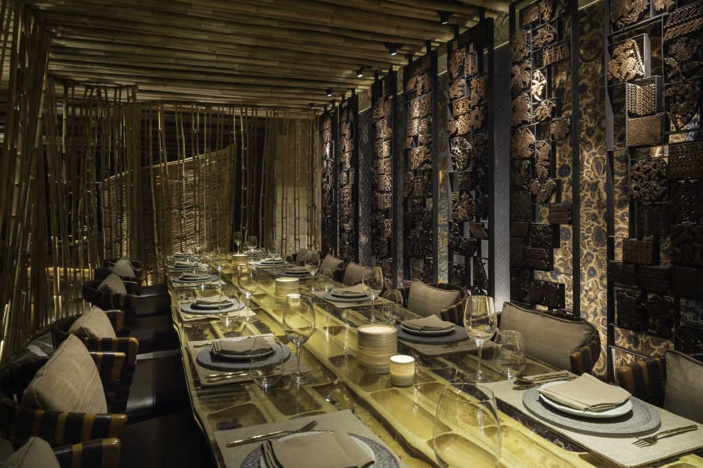 Semi-private dining room with antique batik tjap wall feature by Ibuku